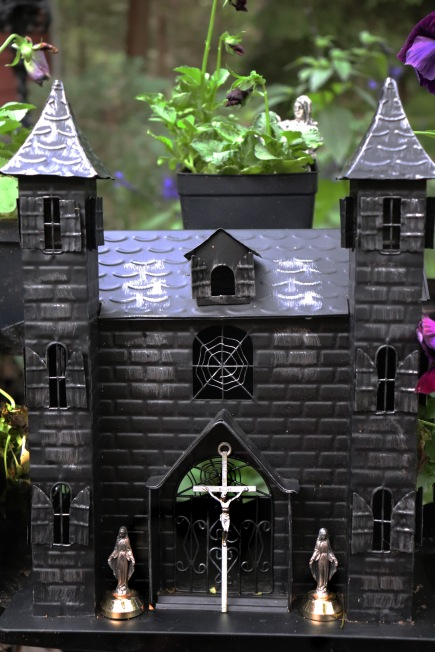 Miniature Gothic cathedral amid purple blooms