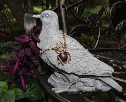 Statues add an important touch to a Gothic garden, this pigeon statue is posed with a stag beetle necklace from www.insectdiva.com and Salvia splendens flowers